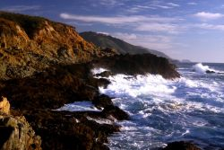 A wave breaking against the rocks of the Granite Canyon area along the Big Sur coastline Photo