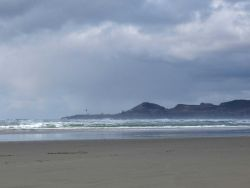 The beach at Newport with Yaquina Head Lighthouse in the distance. Photo