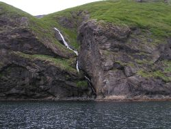 A small waterfall finding its way to the sea on a Shumagin Island. Photo