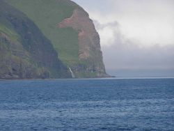 A waterfall rushing to the sea between impressive Aleutian cliffs. Photo