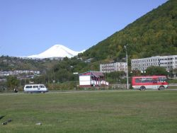 A street scene in Vladivostok with a volcano in the background. Image