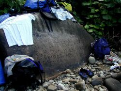 A historical boulder on the beach at Isla Cocos having carvings of names and dates of past visitors to the island Image
