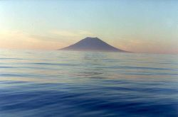 A symmetrical volcanic cone in the Kurile Islands seen at dawn over a calm north Pacific Ocean. Image