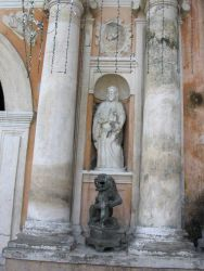 A gargoyle statue and a saint statue adorning San Augustin Church. Photo