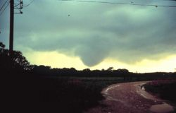 A funnel cloud approaching the ground. Image