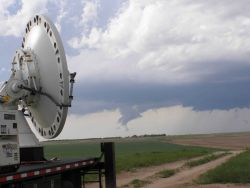 Later that evening, the remants of the tornadic storm are seen with a radar antenna in the left foreground. Photo