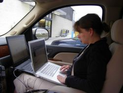 NSSL's Susan Cobb works on two laptops to upload video to a network TV station. Photo