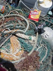 Scuba gear, remains of lunch, and derelict net on small craft prior to return to ship. Photo