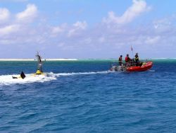 Oceanographers tow a CREWS buoy through a channel for deployment inside an atoll . Photo