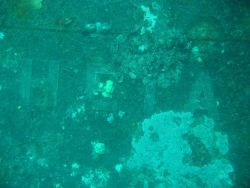 A portion of the Roman letters on the bow of the Heian Maru, a passenger vessel converted to a submarine tender. Image