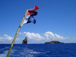 Flags denoting divers down with the islets of Motu Iti and Motu Nui in the background. Photo