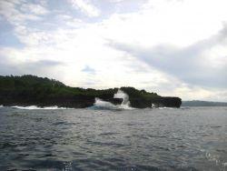 Large swells striking a rocky headland. Photo
