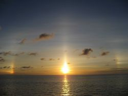 Sunset at sea with sun dogs on each side of the setting sun Photo