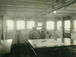 Pilot house of USC&GS Ship HYDROGRAPHER showing bridge control for propulsion motor, automatic steering, gyro-compass repeater, clear vision disc, and Photo