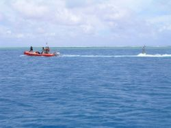 Oceanographers tow a CREWS buoy through a channel for deployment inside of an atoll lagoon. Photo