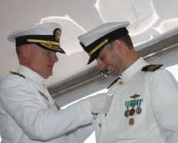 Rear Admiral Michael Devany pins the command at sea pin on Lieutenant Commander Ben Evans, the brand-new commanding officer of the just commissioned N Photo