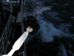 Picking up small boat while underway in moderate seas offshore Kodiak. Photo