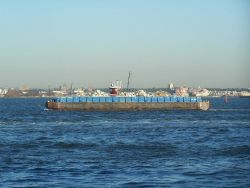 Tug towing garbage barge alongside Photo