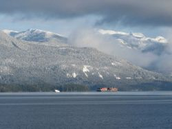 Tug and barge in the Inside Passage after a dusting of snow on the mountains. Photo