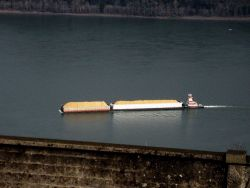 A push boat on the Columbia River pushing what appears to be loaded barges of sand. Photo
