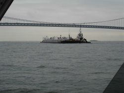 Tug pushing barge ahead under Verrazano Narrows Bridge. Photo
