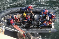 United States Coast Guard rigid-hull inflatable boat discharging personnel on NOAA Ship PISCES. Photo