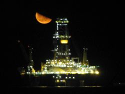 A view of a Deepwater Horizon disaster relief drill vessel with a half moon rising? setting? Photo