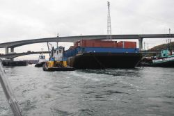 Container barge WESTERN 7 being maneuvered through narrow waterways. Photo