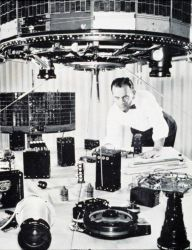 Scientist inspecting early TIROS satellite components Photo