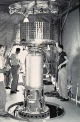 Mounting early TIROS satellite on nose of rocket prior to launch Photo