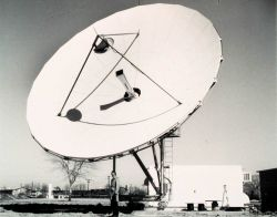 John Hussey, TIROS-N Ground System Project Manager, standing below 36-ft (11-meter) antenna Photo