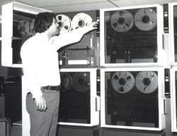 Scientist Frank Porto at the tape drives of the then new National Environmental Satellite Service (NESS) mass data storage system, the SDC TBMII Photo