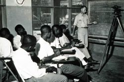 Commander George Morris instructing Liberian engineering students in the use of surveying instruments. Photo