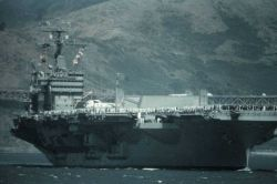 An aircraft carrier in San Francisco Bay fills the field of view Image
