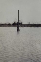 Determining sea level - just kidding! Rodman at bench mark covered by floodwaters Photo