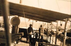 Hauling in sounding line of trolley rig using hand crank on boat deck Photo