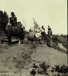 Cable drum being pulled by horses across dunes Photo