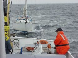 NOAA Ship RUDE towing a disabled sailboat into a safe harbor. Photo