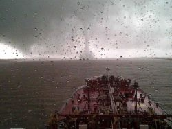 Tornadic waterspout crossing Mississippi River in front of large moving ship on the Mississippi River Photo