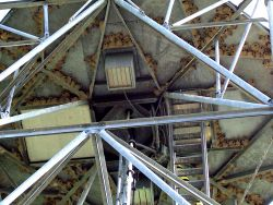 Bottom of the radome (part of pedestal structure) with many barn swallow nests. Photo
