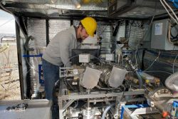 Theran Riedel from the University of Washington checks instruments inside the elevator-mounted laboratory that travels up and town the 1,000 foot towe Photo