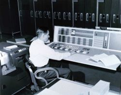 A meteorologist at the console of the IBM 7090 electronic computer in the Joint Numerical Weather Prediction Unit Photo
