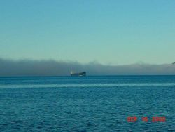 A tanker passing out of a fog bank. Image