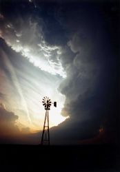 A windmill standing alone against a supercell thunderstorm. Image