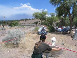National Weather Service IMET trainee Valerie Myers positioning the Direcway satellite dish while smoke from the Bear Fire is seen in the distance. Photo