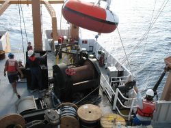 While the clouds approach and the TAO buoy streams aft with attached line, the deck crew of the NOAA Ship GORDON GUNTER move a second TAO to its pre-m Photo
