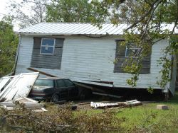 A house either floated off its foundation or was blown off its foundation and landed on this vehicle Image