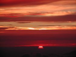 The sun drops between layers of clouds as another day of measurements ends at the Mauna Loa Observatory. Photo