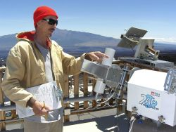 Steve Ryan points to an instrument that measures the intensity of sunlight at the Mauna Loa Observatory. Photo