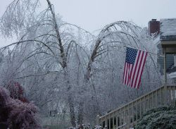 American flag hanging proudly from the porch of a home during a devastating ice storm Image